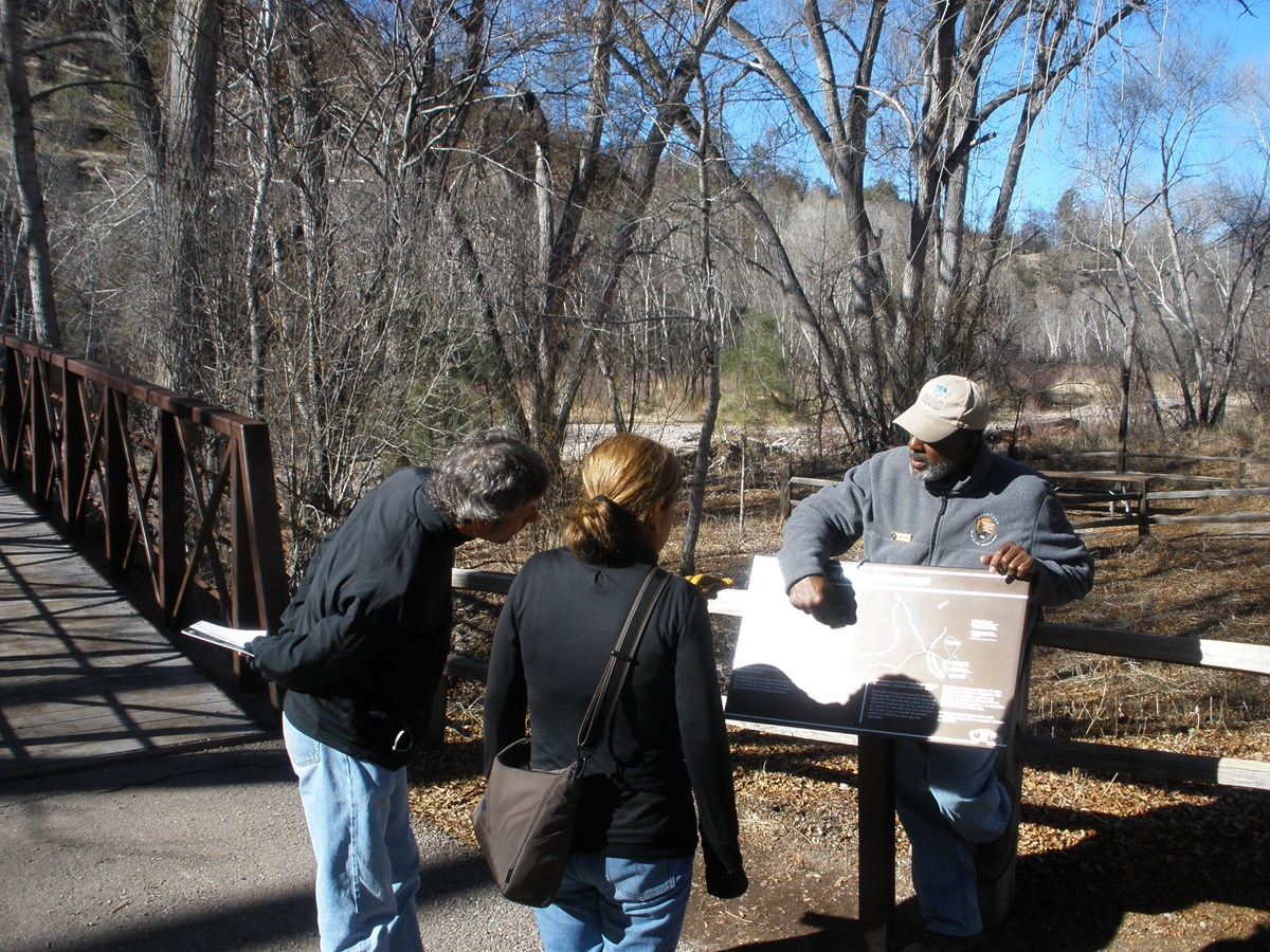 A volunteer ranger orients visitors to the trail conditions at Cliff Dweller Canyon trailhead.