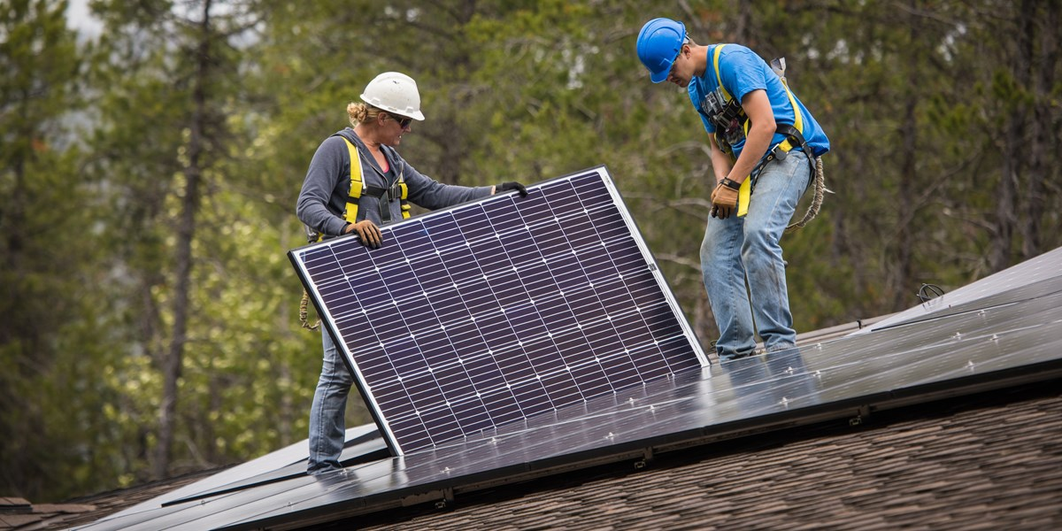 People install solar panels on a roof.
