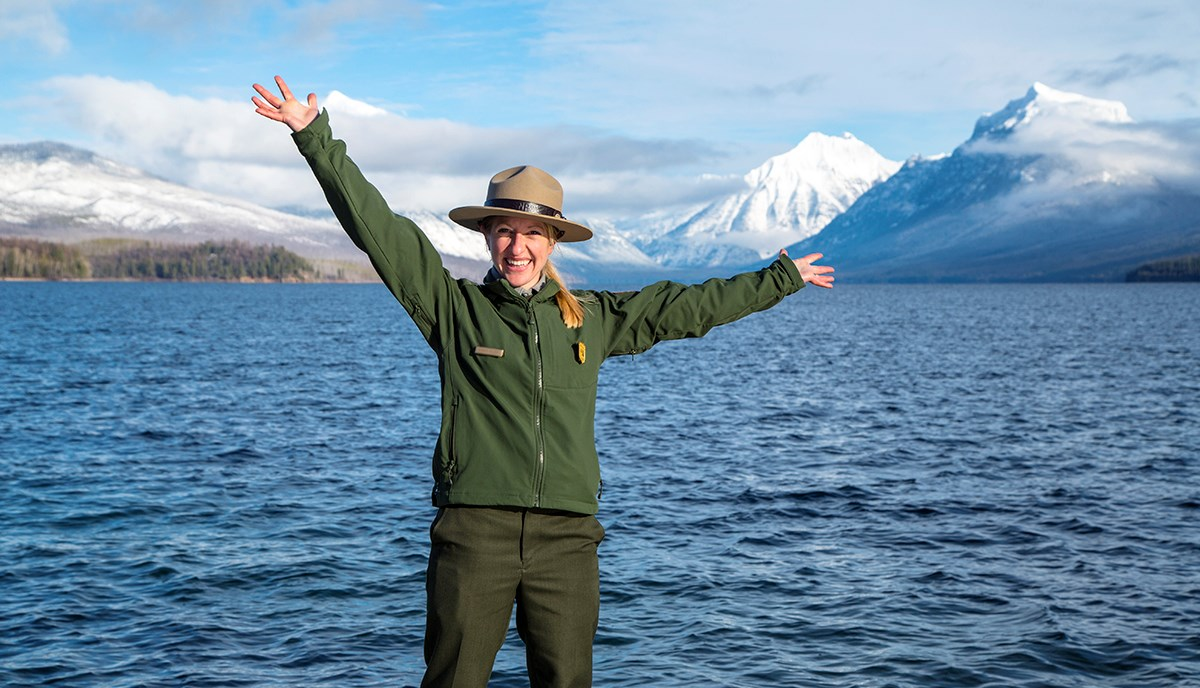 Smiling ranger stands in front of lake and mountains with arms outstretched