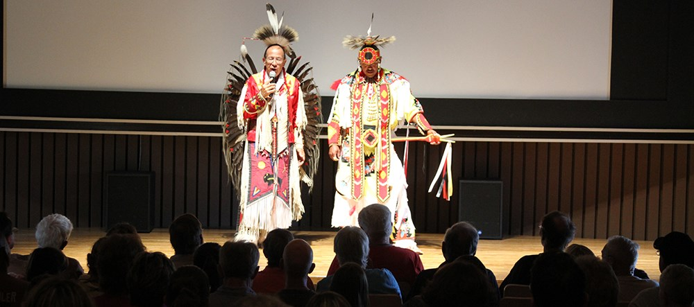 audience members in silhouette as two tribal members in ceremonial dress stand on stage