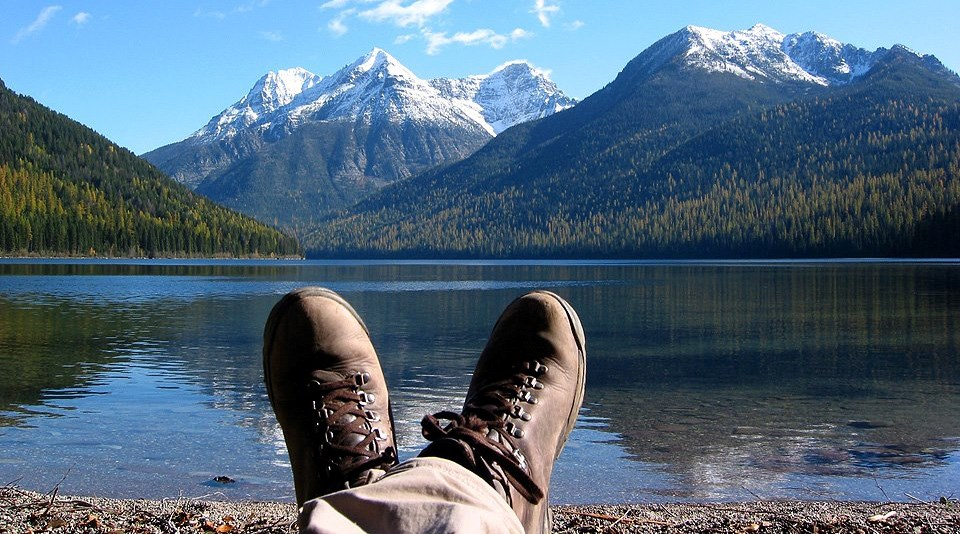 crossed boot-clad feet by shore of mountain lake