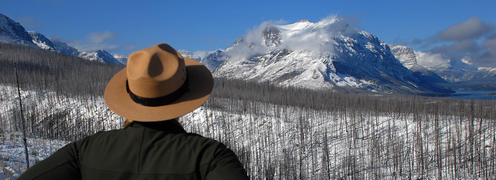 Ranger wearing flat hat faces snow covered mountain vista