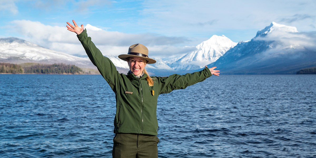 Ranger with arms spread out in joy at working in Glacier National Park