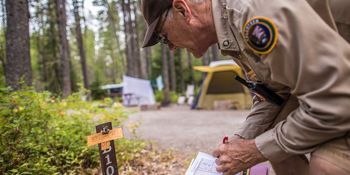 A campground host bends down to check on a campsite registration stub