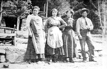 Historic image of man and three women in long skirts and aprons standing outside