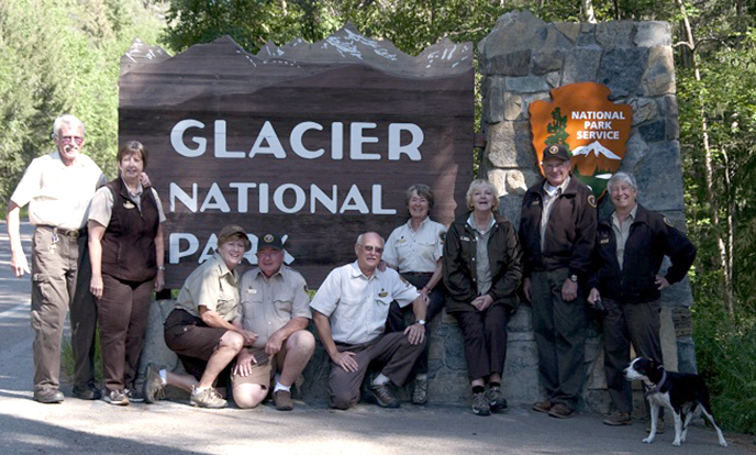 Group of volunteers gathered around park entrance sign