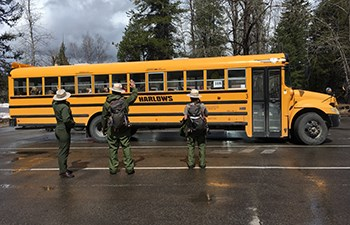 Three rangers wave as a school bus pulls into a parking lot