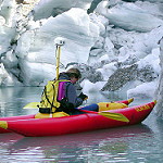 researcher in boat takes notes by glacier