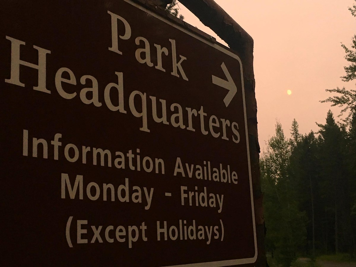 A photograph of Glacier National Park Headquarters sign with an arrow pointing.
