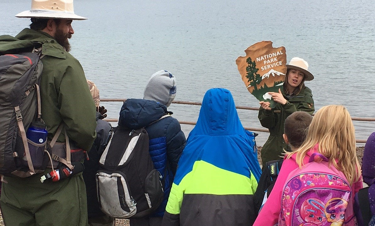 Ranger watches over line of students by a lake while another ranger holds up NPS arrowhead and points to the bison