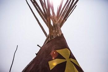 Sunlight through lodgepoles sticking out of top of tipi