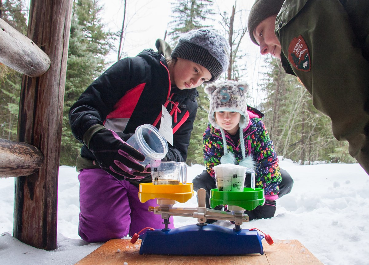 A ranger and two students use a scale to measure cups of snow and water.