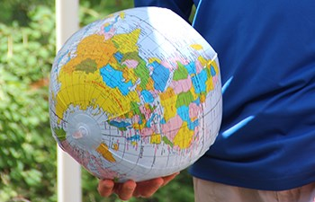 Hand holding an inflatable globe