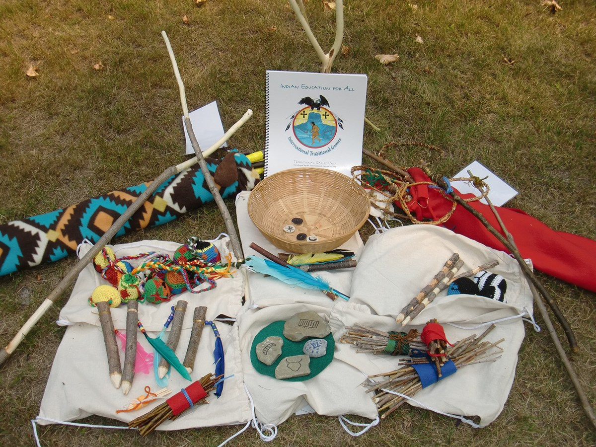 basket, sticks, antlers, and other game pieces arranged on grass