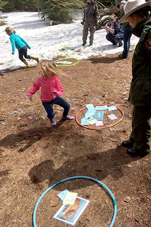 Ranger stands by hoops on ground filled with documents as little girls run about