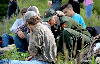 Uniformed employee crouches by students with notebooks in field