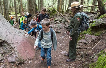 children on trail with ranger look at large rock