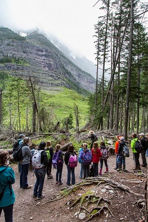 School group on trail faces ranger as she points up a mountainside