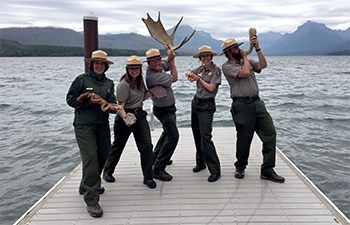 Rangers goof around on dock with antlers, rocks, sticks, and horn