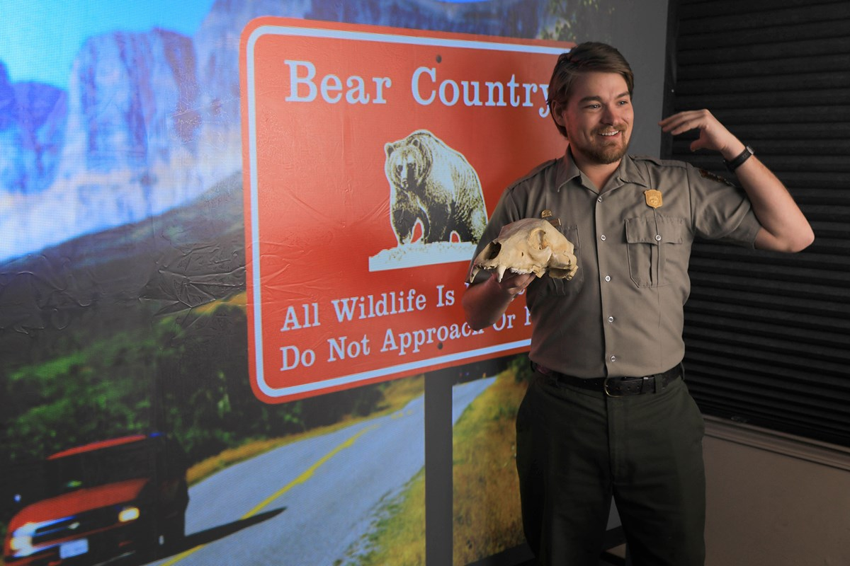 Park ranger holding bear skull stands in front of screen with Bear Country sign projected on it