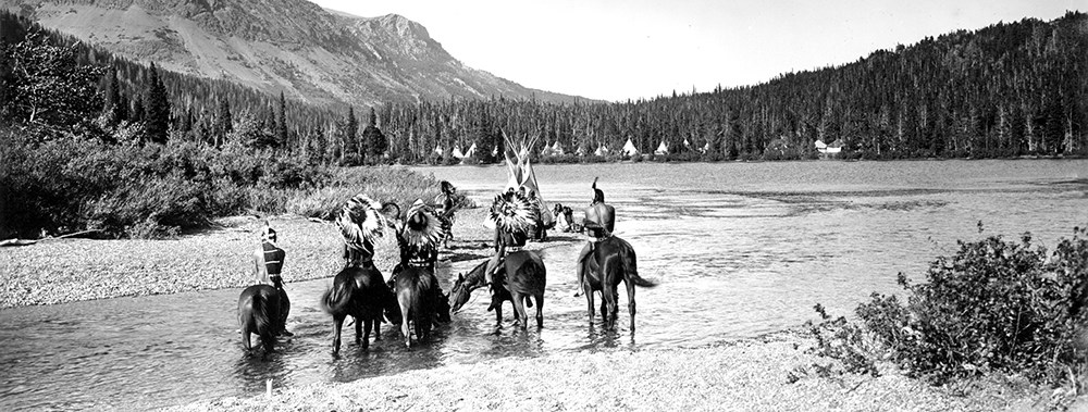 Five Native Americans on horseback cross mountain stream toward camp