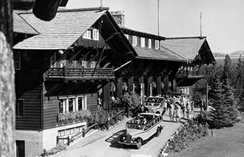 historic image of buses, people and grounds in front of wooden hotel with balconies