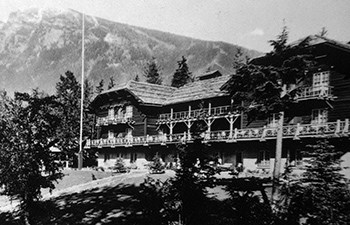 historic image of multistory hotel on grassy hill with mountain in background