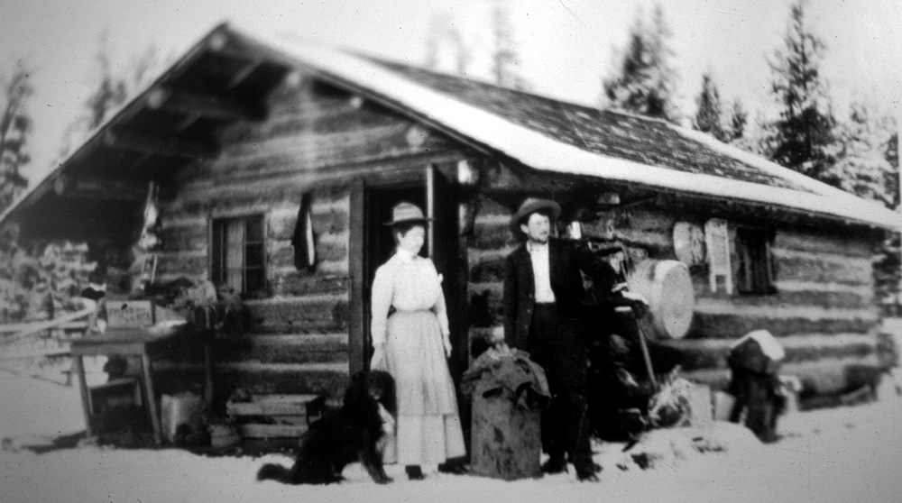 woman, man, and dog in front of rustic log cabin