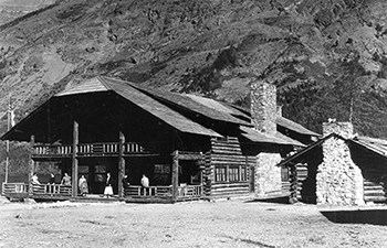 historic image of people on porch of large 2 story log building with smaller log cabin beside
