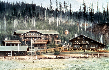 tinted historic slide of multiple wooden buildings adorned with antlers