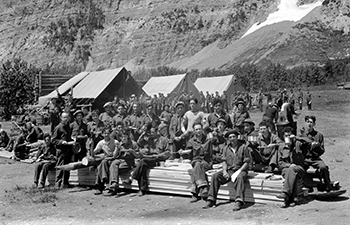 group of young men holding camp cookware, canvas tents in background