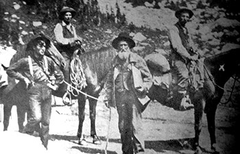 historic image of group of men, some on horse back, bearded man center