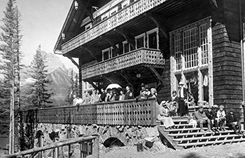 historic image of people in period dress on porch of large wooden building with mountains in background