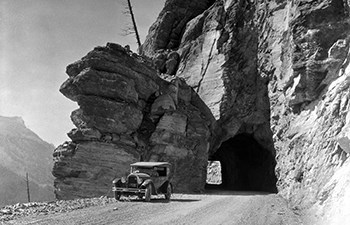 black and white photo of early 1900s car by tunnel in rocky cliff