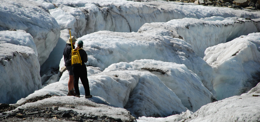 two researchers stand at edge of glacier