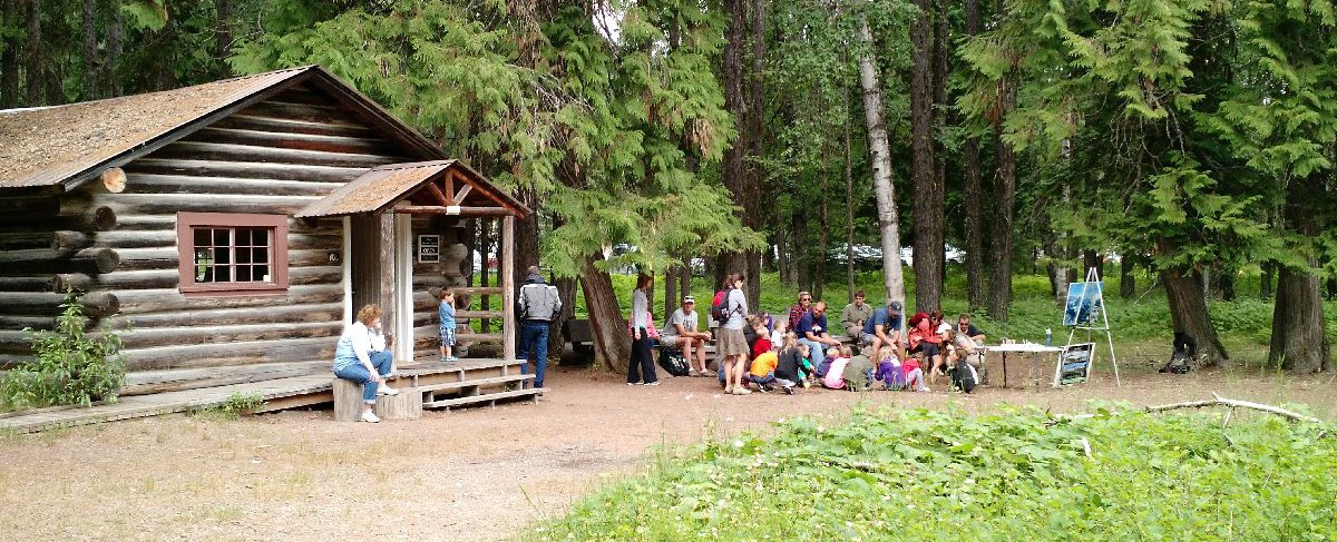Group of children and adults outside small cabin in forest setting