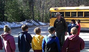 Group of students listen to ranger, with school bus parked in background