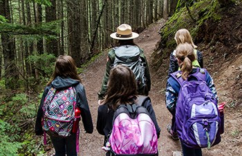 Girls with backpacks follow ranger down trail