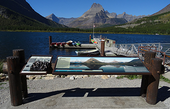 Panoramic wayside and bronze tactile by boat dock on mountain lakeshore