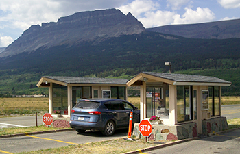 Car in lane between fee booths; mountain in background