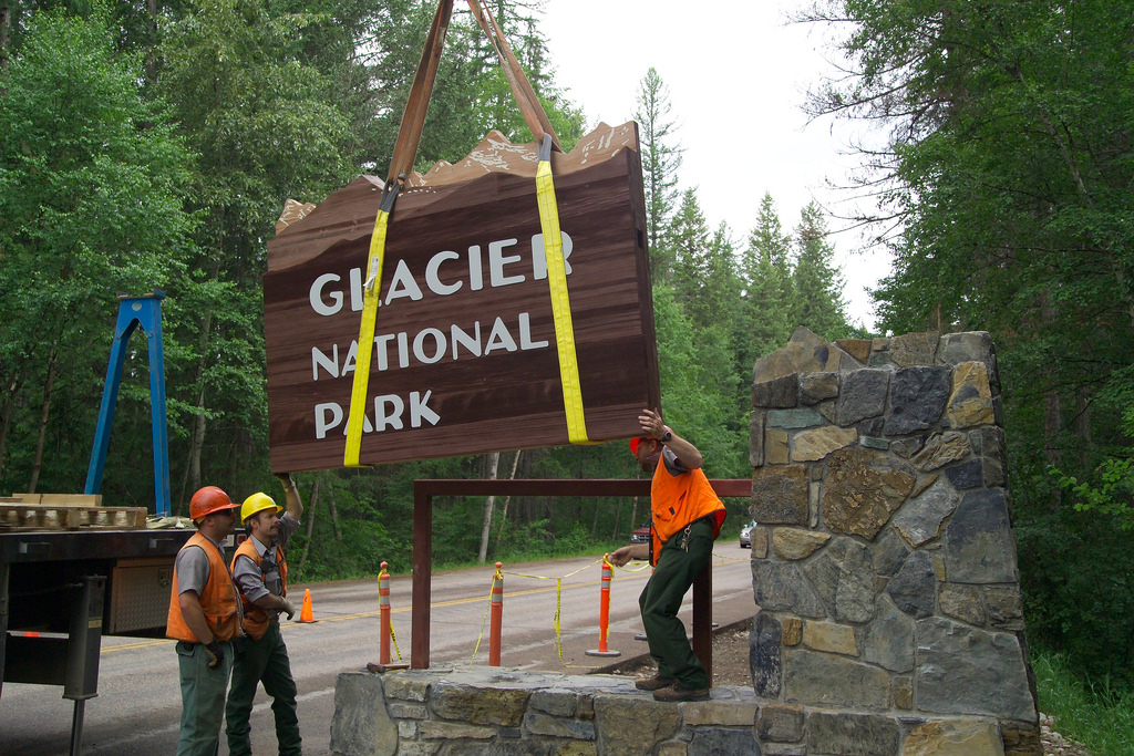 uniformed workers use crane truck to install wooden entrance sign