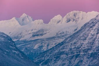 Pink sky sunset over snowy mountains.