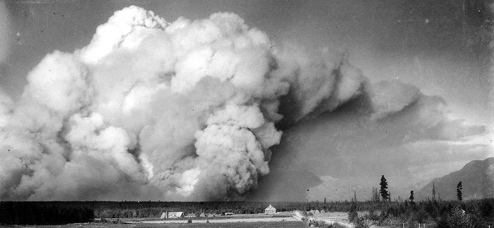 Historic image of huge smoke plum over tiny trees and buildings