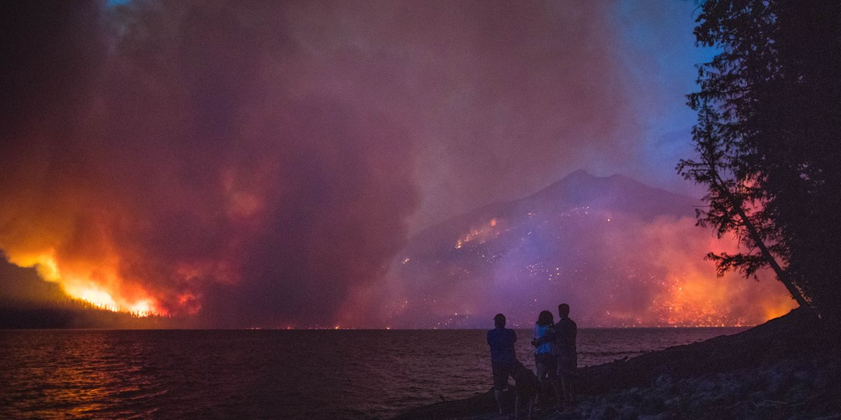 Three people standing on a lake shore watching a huge wildfire at night.