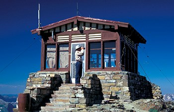 man with binoculars on stone steps of lookout building