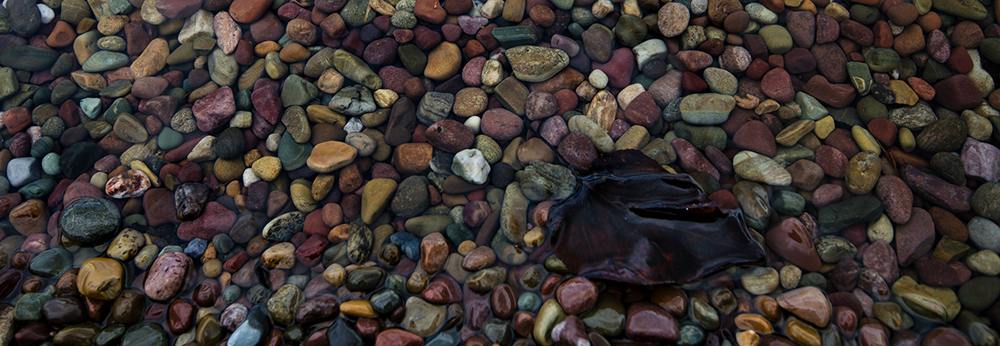 close-up of many colored rocks below water surface