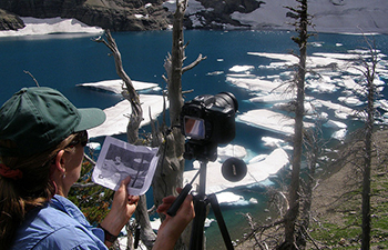 photographer holds historic photo next to camera at icy lake