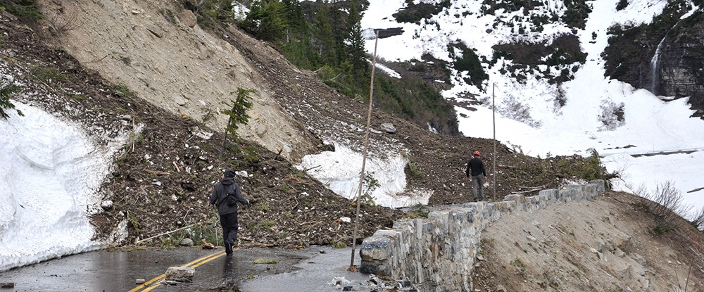 debris and snow piled on road in front of workers
