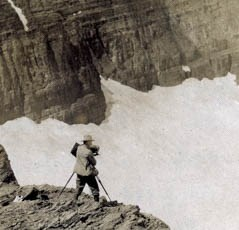 A man stands on a cliff with a camera.