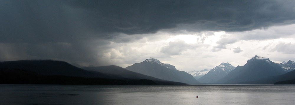 storm moving left to right over mountain lake